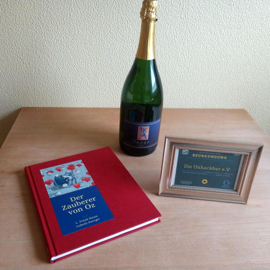 """Das Buch """"Der Zauberer von Oz"""", eine Urkunde und eine große Flasche Sekt"""